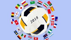 Ein Fußball mit der Aufschrift 2018. Rund um den Fußball sind die Nationalflaggen der beteiligten Nationen eingesteckt.